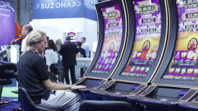 Attendees play slot machines at the Global Gaming Expo inside the Venetian Macau resort and casino operated by Sands China Ltd a unit of Las Vegas...