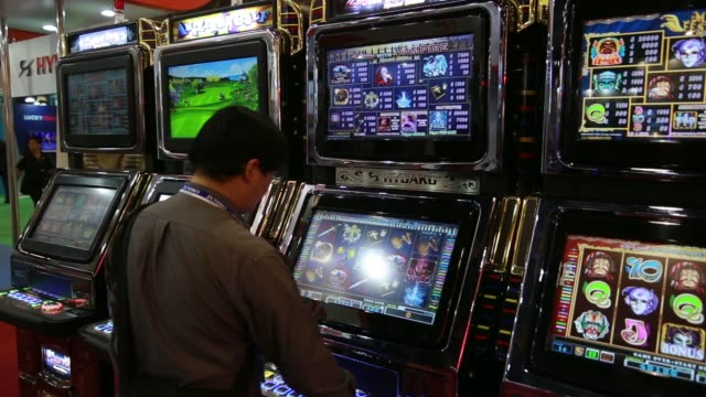 ws attendees play slot machines ms numbers and icons are illuminated on a slot machine ws attendees play gaming machines ws players sit at an... - blackjack stock videos and b-roll footage