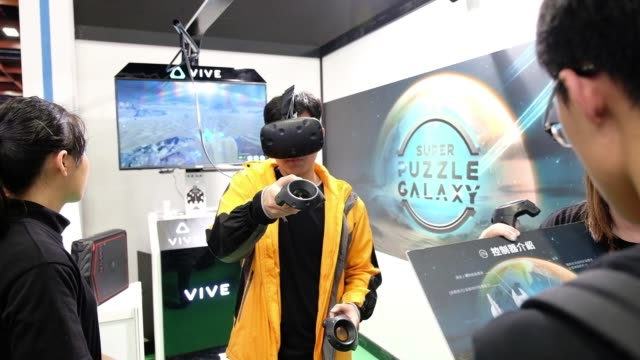 stockvideo's en b-roll-footage met attendees play video games during the 2018 taipei game show in taipei, taiwan, on friday, jan. 26 an attendee uses a vive virtual reality headset,... - television game show