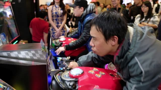 attendees ride on the international games system co. speed rider 3 twin racing machine during the 2018 taipei game show in taipei, taiwan, on friday,... - television game show stock-videos und b-roll-filmmaterial