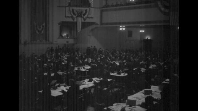 attendees seated at long tables at committee for industrial organization with mounds of paper; men hold papers upright, ; hall decorated with... - trade union stock videos & royalty-free footage