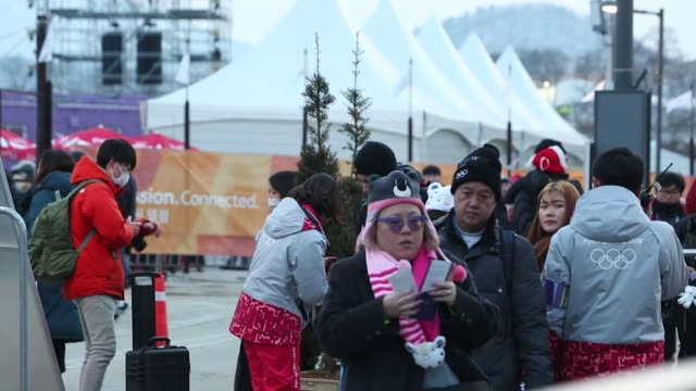 Attendees show tickets to volunteers as they enter the PyeongChang Olympic Plaza ahead of the opening ceremony of the 2018 PyeongChang Winter Olympic...