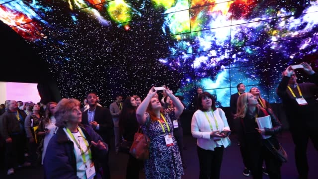 vidéos et rushes de attendees take photographs with mobile devices while standing under a tunnel wall of lg oled 4k tvs during the 2017 consumer electronics show in las... - exposition et salon professionnel