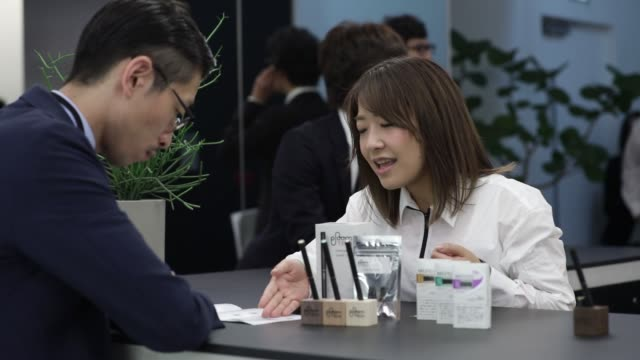 attendees try out japan tobacco inc's ploom tech smokeless tobacco devices during a media preview at the company's ploom shop ginza in tokyo japan on... - 煙草製品点の映像素材/bロール