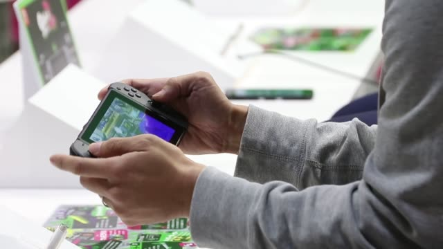 """vidéos et rushes de attendees try the video game """"splatoon 2"""" on nintendo co.'s switch video-game consoles at an unveiling event in tokyo, japan, on friday, jan. 13,... - switch"""