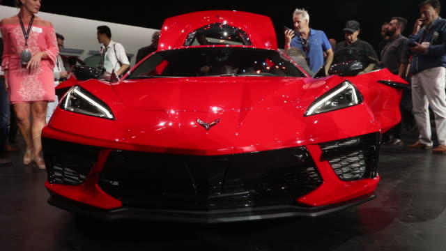 Attendees view the engine of a General Motors Co 2020 Chevrolet Corvette sports car as it sits on display after a reveal event in Tustin California...