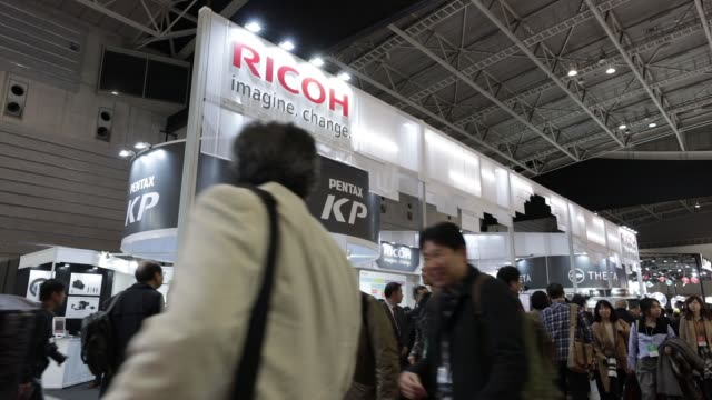 attendees visit the ricoh co booth at the cp camera and photo imaging show in yokohama kanagawa prefecture japan on friday feb 24 the ricoh co logo... - digital camera stock videos and b-roll footage