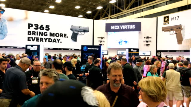attendees visit the sig sauer booth during the nra annual meeting exhibits at the kay bailey hutchison convention center on may 5 2018 in dallas... - national rifle association stock videos & royalty-free footage