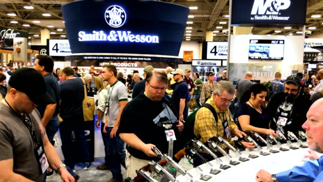 attendees visit the smith and wesson booth during the nra annual meeting & exhibits at the kay bailey hutchison convention center on may 5, 2018 in... - arma da fuoco video stock e b–roll