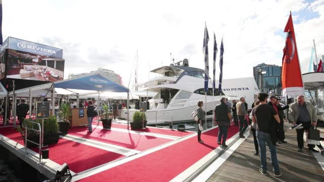 Attendees walk along a jetty as yachts sit on display during the Sydney International Boat Show in Sydney Australia on Thursday Aug 3 Boats...