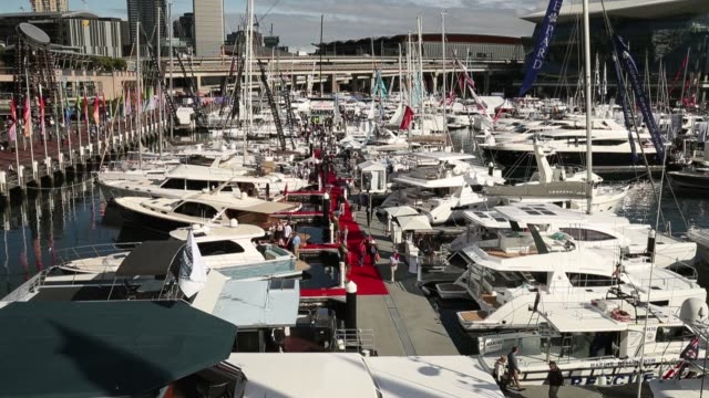 Attendees walk along a jetty as yachts sit on display during the Sydney International Boat Show in Sydney Australia on Thursday Aug 3 Yachts sit on...