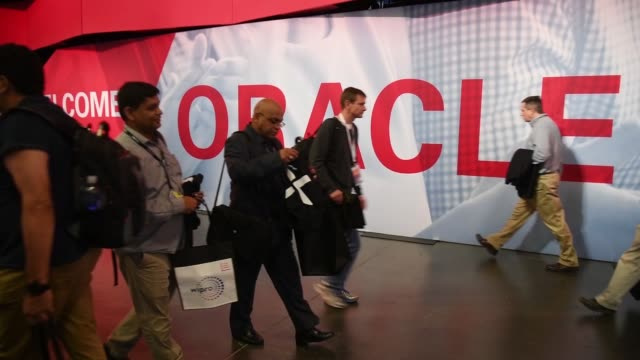attendees walk inside the oracle openworld 2017 conference and pass large signage in san francisco california us on monday oct 2 2017 photographer... - oracle corporation stock-videos und b-roll-filmmaterial