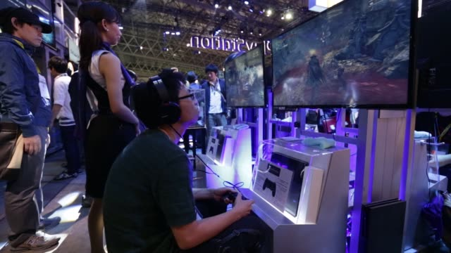 stockvideo's en b-roll-footage met attendees walk past a sony computer entertainment inc. booth displaying a playstation logo at the tokyo game show 2015 at makuhari messe in chiba,... - television game show
