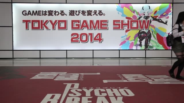 attendees walk past signage displayed at the entrance to the tokyo game show 2014 in chiba, japan, attendees try video games at the tokyo game show... - game show stock videos & royalty-free footage