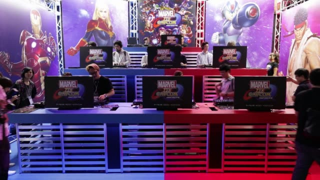stockvideo's en b-roll-footage met attendees walk past the capcom co. booth displaying the marvel vs capcom: infinite video game at the tokyo game show 2017 at makuhari messe in chiba,... - television game show