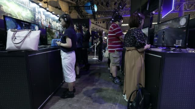 attendees walk past the square enix co. booth at the tokyo game show 2017 at makuhari messe in chiba, japan, on friday, sept. 22 attendees play the... - game show stock videos & royalty-free footage