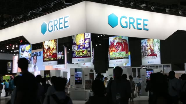 vídeos de stock, filmes e b-roll de attendees walk under signage for gree inc at the tokyo game show 2013 in chiba japan on thursday sept 19 employees hand out bags at the gree inc... - game show