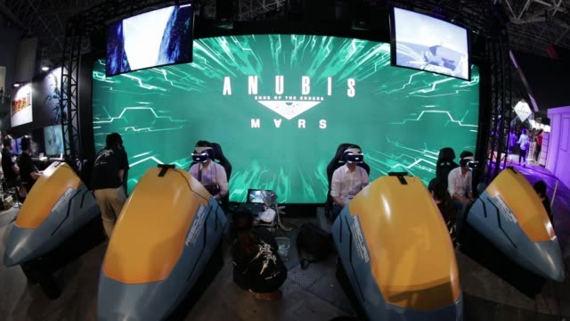 vídeos de stock, filmes e b-roll de attendees wear sony corp. playstation vr headsets as they play the zone of the enders: anubis mars video games in the konami corp. booth in this... - game show