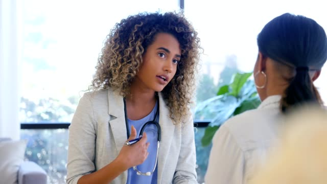 attentive female doctor talks with patient about the patient's symptoms - general practitioner stock videos & royalty-free footage