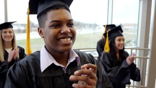 attentive group of graduates applaud during graduation ceremony - graduation stock videos & royalty-free footage