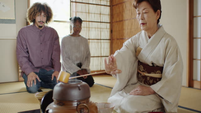 attentive guests watching hostess prepare tea at traditional tea ceremony - washitsu stock videos and b-roll footage