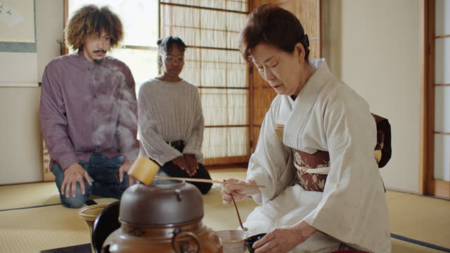 attentive guests watching hostess spoon matcha from caddy into bowl at traditional tea ceremony - washitsu stock videos and b-roll footage