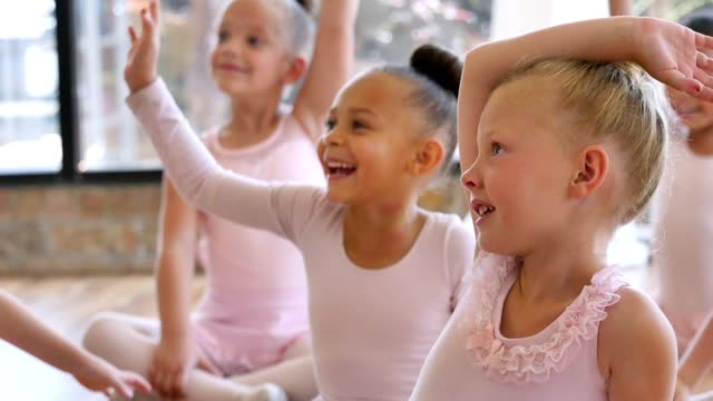 Attentive young ballerinas answer ballet teacher's questions before class