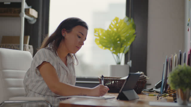 attentive young woman jots down notes as she participates in a video conference call - workshop stock videos & royalty-free footage