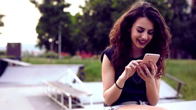 attracitive ung flicka med smartphone utomhus - endast en tonårsflicka bildbanksvideor och videomaterial från bakom kulisserna