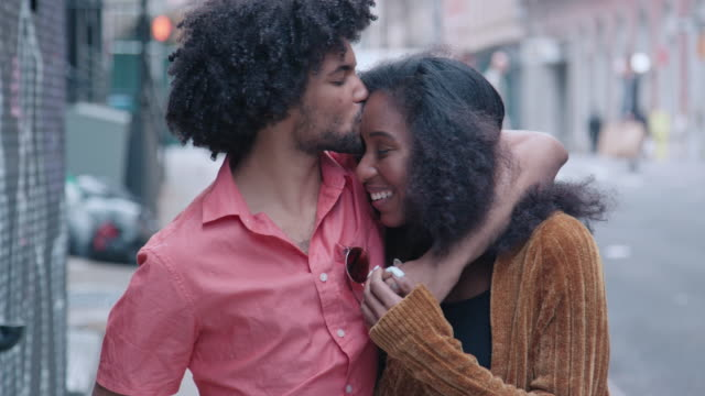 attractive african american couple walk and show affection on urban street - african american ethnicity stock videos & royalty-free footage