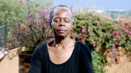 Attractive African American senior woman meditating outdoors