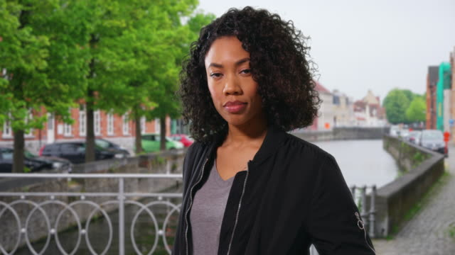 Attractive African American woman on vacation standing beside canal in Bruges