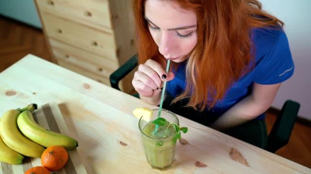 Aantrekkelijk en verse roodharige vrouw kijken 20s gezond vruchtensap drinken