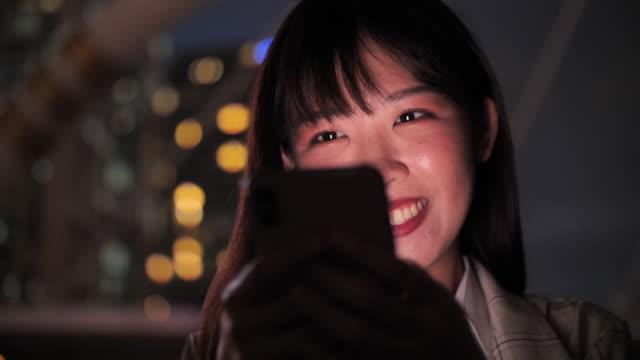 路上を歩いている間に携帯電話を使った魅力的なアジアの女性 - 市街地の道路点の映像素材/bロール
