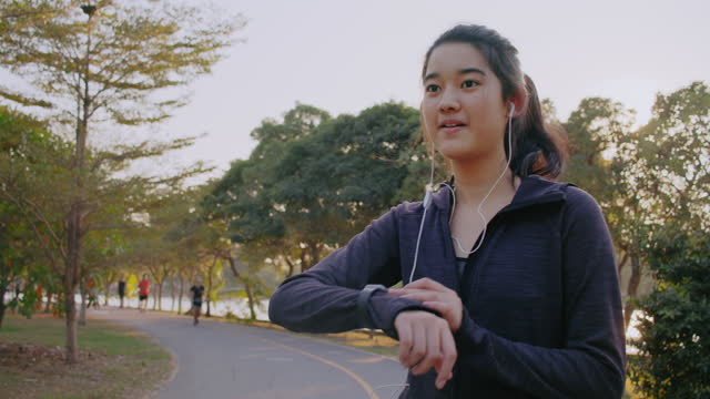 attractive asian adult man running or jogging in the city. man stop running and checking on his smart watch - monitoring equipment stock videos & royalty-free footage