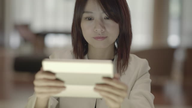 Attractive Asian Businesswoman Communicating with Portable Information Device. Using Tablet Technology in Lounge.