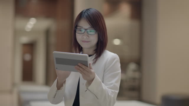 attractive asian businesswoman communicating with portable information device. using tablet technology in lounge. - mittellanges haar stock-videos und b-roll-filmmaterial