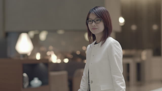 attractive asian businesswoman wearing glasses and waiting in lounge. standing on floor. - mittellanges haar stock-videos und b-roll-filmmaterial