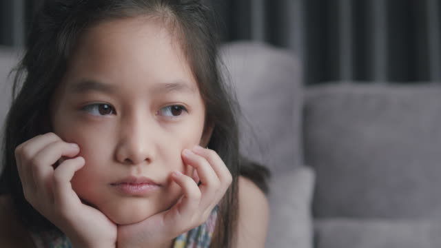 attractive asian child girl feel sad and depressed from her relationship with friends cyberbullying. tween girl depressed hispanic about her online learning and education exam score while sitting in the living room at home. - orphan stock videos & royalty-free footage