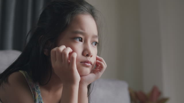 attractive asian child girl feel sad and depressed from her relationship with friends cyberbullying. tween girl depressed hispanic about her online learning and education exam score while sitting in the living room at home. - kids stock videos & royalty-free footage