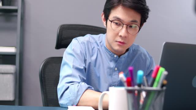 魅力的なアジア人男性フリーランスラップトップを使用し、昼間にホームオフィスでノートブック紙に彼のプロジェクトの順序を書き留めます。彼の家でラップトップでeラーニングを勉強し - 30代点の映像素材/bロール