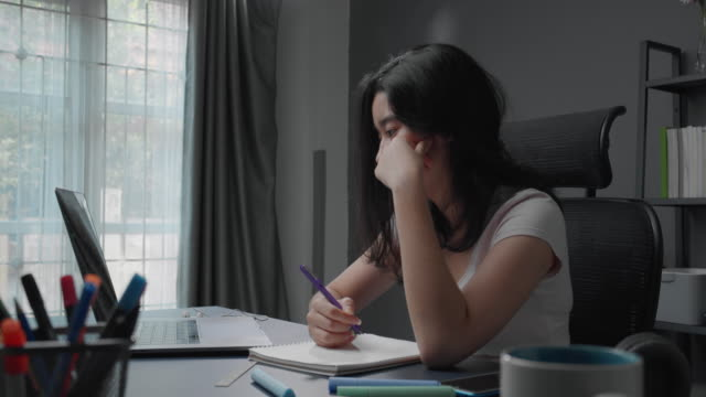 attraktive asiatische teenager-mädchen fühlen sich traurig und deprimiert nach dem lesen und studium online-klasse auf ihrem laptop-computer. homeschool mädchen besorgt über ihre online-lern- und bildungsprüfung punktzahl, während im wohnzimmer zu ha - bedrohung und belästigung stock-videos und b-roll-filmmaterial