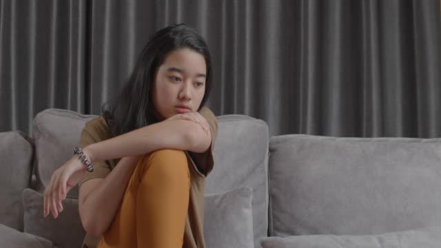 魅力的なアジアのティーンエイジャーの女の子は、友人のサイバーいじめとの関係から悲しいと落ち込んでいます。かわいい女の子自宅のリビングルームに座っている間、彼女のオンライン� - 孤児点の映像素材/bロール