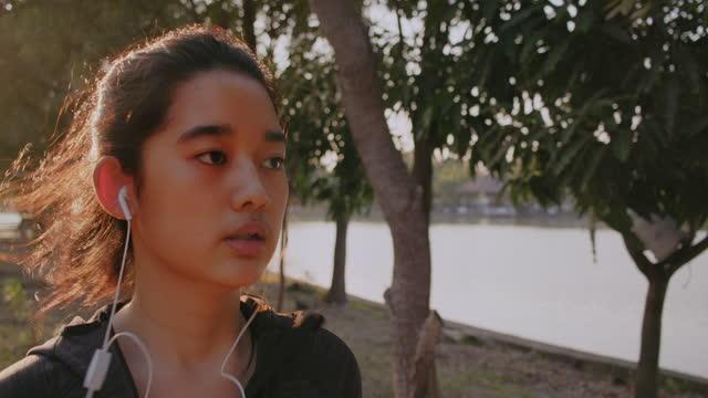 公共の公園で実行しながら、魅力的なアジアのティーンエイジャーの女の子が音楽を聴きます。朝の運動をしている若い女性。 - strength点の映像素材/bロール