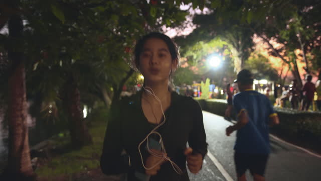 attractive asian teenager girl listening music while running in the public park. young woman jogging exercising in the night time. - listening stock videos & royalty-free footage