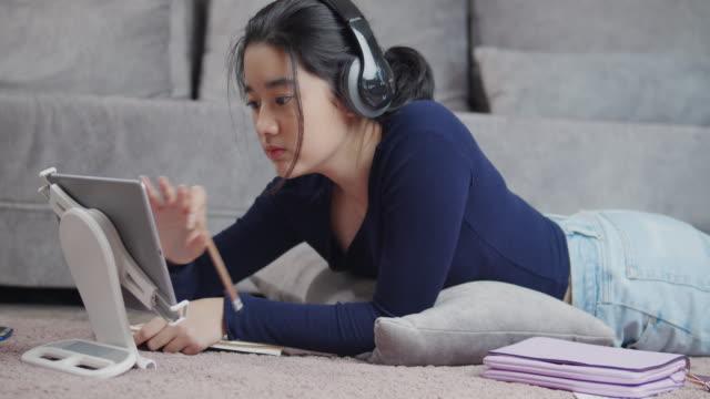stockvideo's en b-roll-footage met aantrekkelijk aziatisch tienermeisje dat hoofdtelefoon het luisteren draagt en online homeschool op tabletscherm met haar leraar bestudeert en op notitieboekjecoronavirus of covid 19 lockdownsituatie schrijft. video gesprek technologie met haar advies om h - e learning