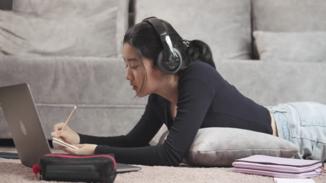 attractive asian teenager girl wearing headphone listening and studying online homeschool on tablet screen with her teacher and writing on notebook  coronavirus or covid 19 lockdown situation. video call technology with her advice to learn her homework. - remote location stock videos & royalty-free footage