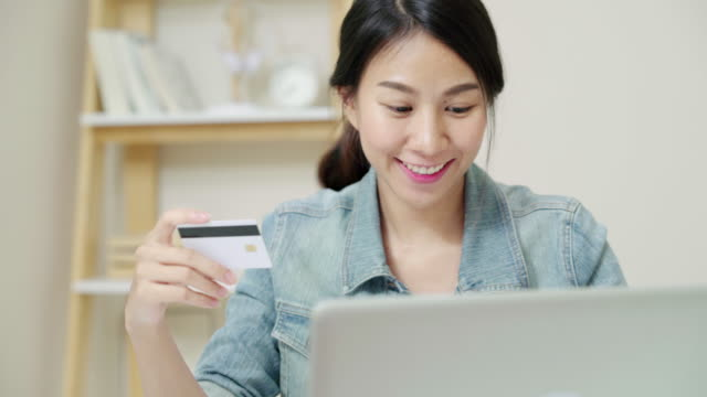 attractive asian woman using credit card paying with laptop computer - credit card purchase stock videos & royalty-free footage