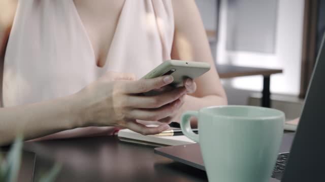 vidéos et rushes de femme asiatique attirante utilisant le smartphone ou le téléphone mobile et l'ordinateur portable tout en travaillant à la maison avec la quarantaine de coronavirus, le verrouillage, le télétravail et les concepts de technologie sans fil - confinement