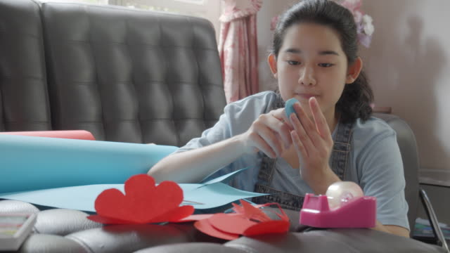 attractive asian young teenager girl wrapping presents for december holiday or christmas present. - christmas wrapping paper stock videos & royalty-free footage